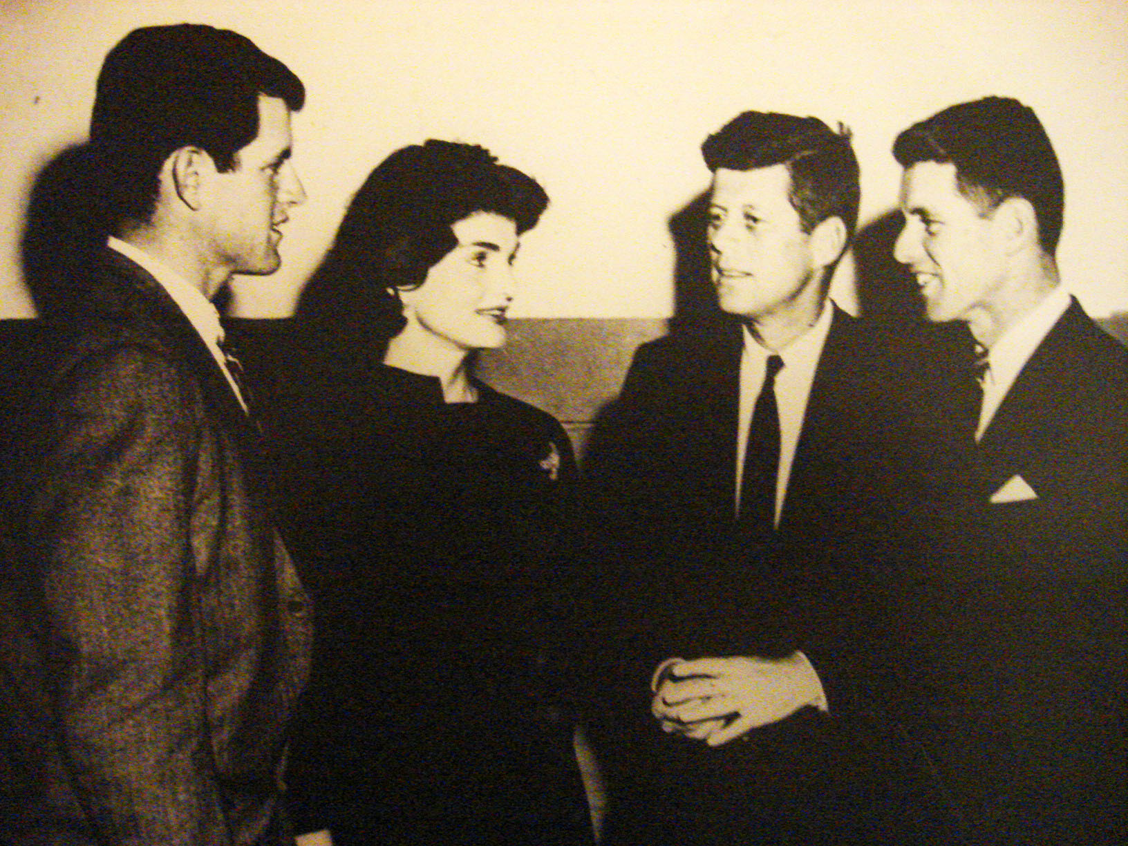 "Edward, Jackie, John and Robert Kennedy at U.Va (from left to right). When Edward Kennedy was a second-year law student, the Law School held its first Law Day. John F. Kennedy (then senator of Massachusetts) spoke on ""The Unknown Challenge,"" discussing foreign and domestic policy. His brother Robert attended as an alumnus. (Photograph by Donna Stapley)"