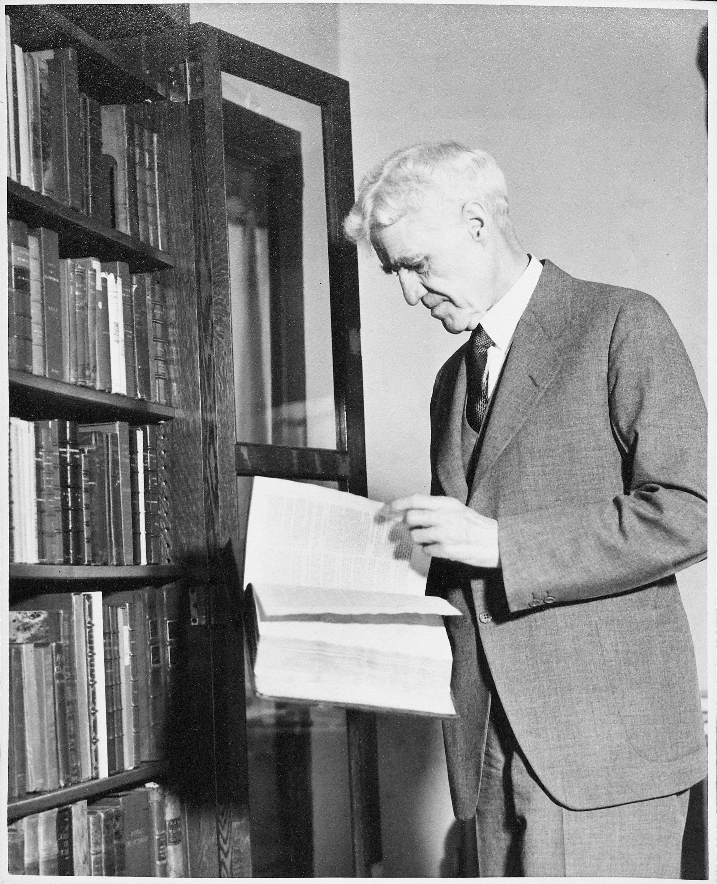 Tracy W. McGregor inspecting a book from his library.