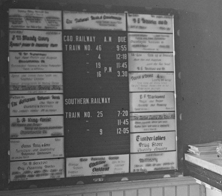 Hand-lettered advertisements for local businesses surround the Charlottesville train timetable in the Gleason Hotel in 1915, detail from a larger photograph. photograph from