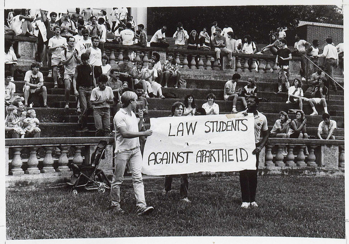 Atcheson Laughlin Hench. Anti-Apartheid Rally. Photograph, 1987 (RG-30/1/10.011) University of Virginia Visual History Collection This photograph, taken in 1987, depicts University of Virginia law students in the McIntire Amphitheatre, peacefully protesting the racially divisive apartheid system in South Africa. Hench, a University professor since 1922, was also a keen chronicler of University life through photography and many of his pictures remain in the University's Visual History Collection. The apartheid government would begin the process of handover to a democratic system three years later in 1990.