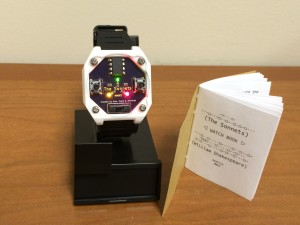 Pictured here is the watch with the instructional booklet open to the title page.