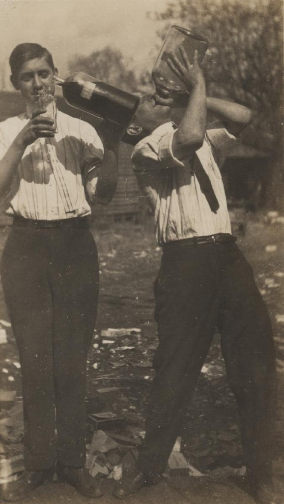 """Guys Drinking."" Hot Foot Society, 1903. (RG-23/46/1.971) University of Virginia Visual History Collection This photograph shows two University of Virginia students drinking alcohol straight from handles. These students were members of a society at the University of Virginia, formally known as the Hot Foot Society. The Hot Foot Society, which began in 1902, was known for its heavy participation in drinking. After their first suspension in 1908, the Hot Foot Society decided to disband in 1911, following a prank which resulted in the expulsion of four members and one-year suspensions for another four members. In 1913, the society reincarnated itself into the IMP Society, which remains active today."