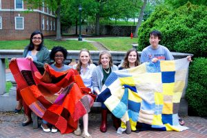 Warm Up America students posing on Grounds with quilt