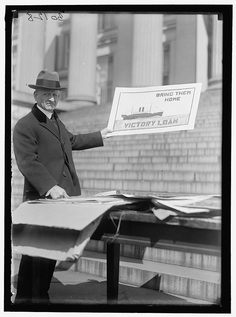 """Photograph of Carter Glass with poster for Victory Loan program: """"Bring Them Home"""""""